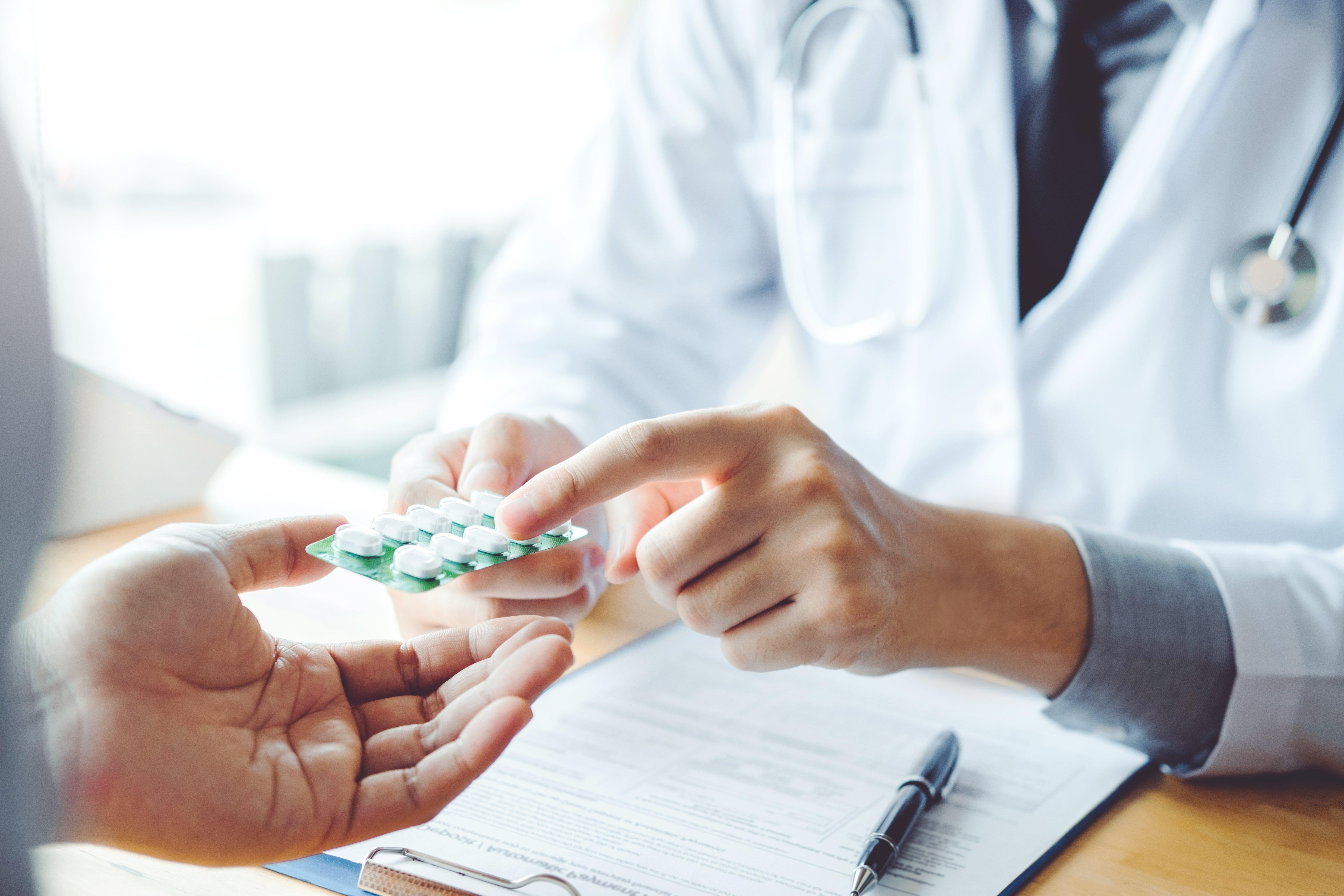 doctor handing patient prescription pills
